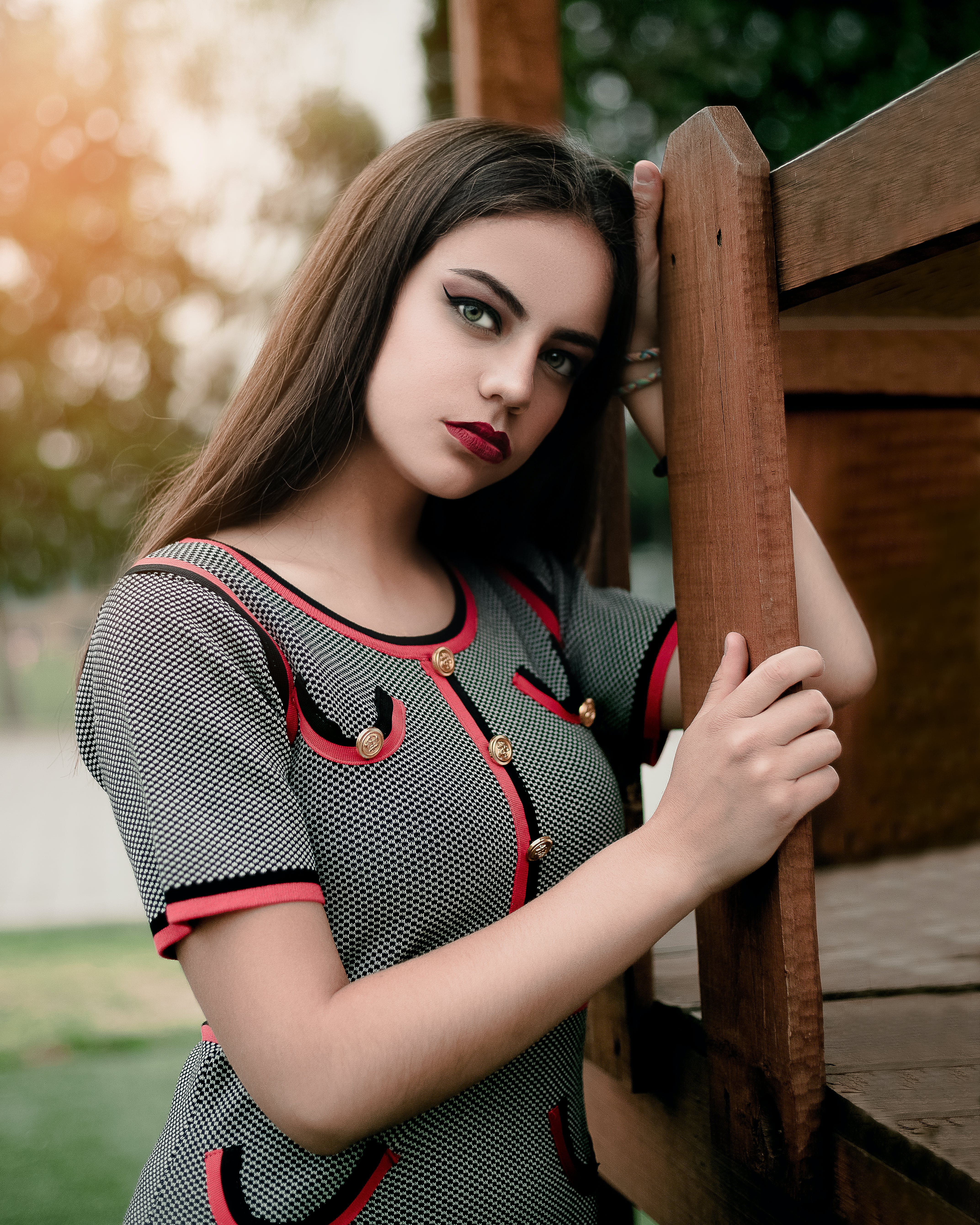 Photo of Woman Leaning On Wooden Fence