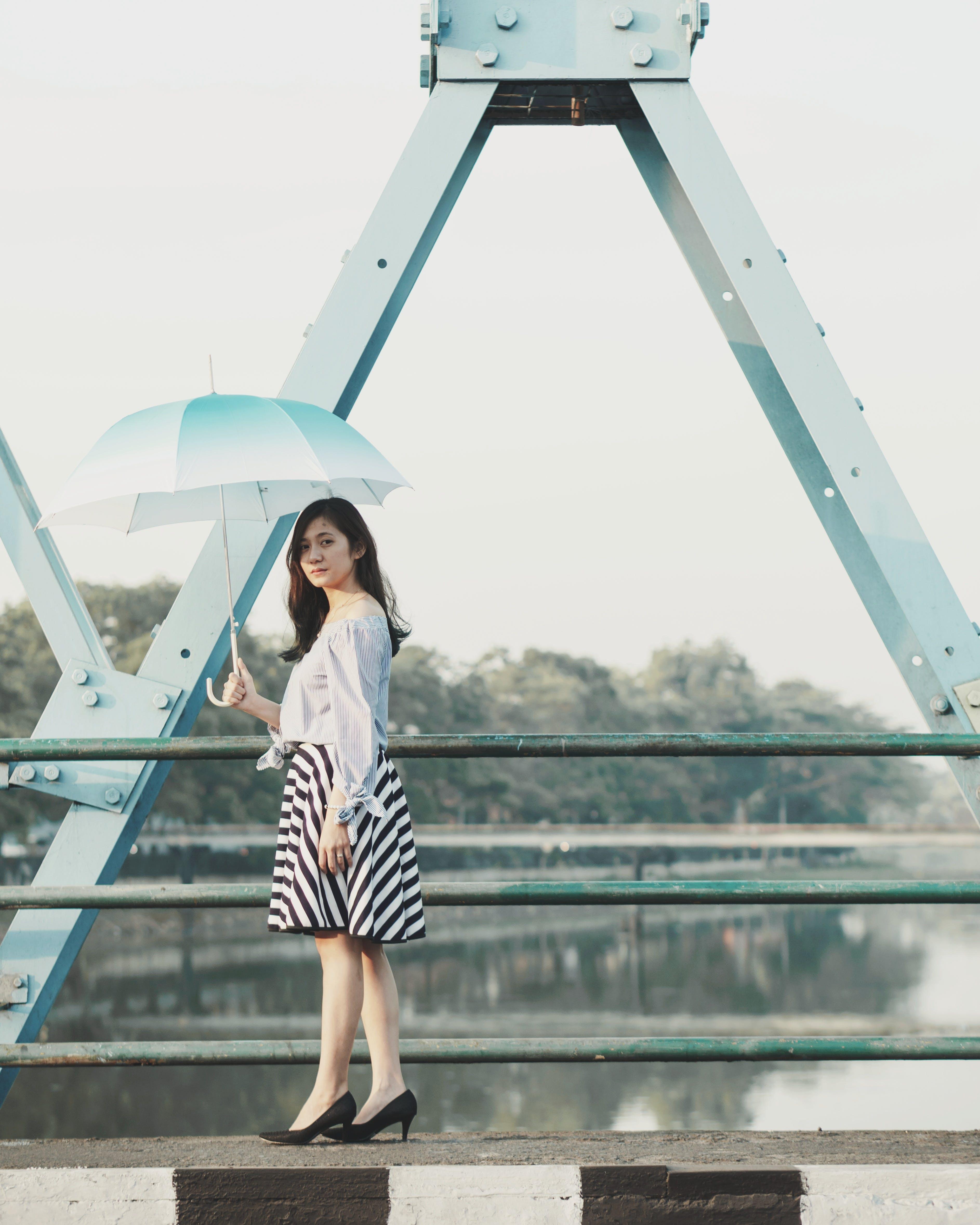 Photo of Woman Holding Umbrella on Bridge