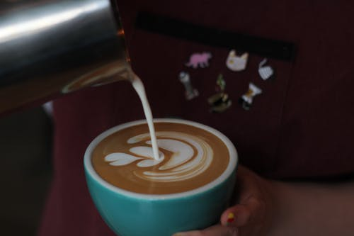Close-Up Photo of Person Pouring Milk In Coffee