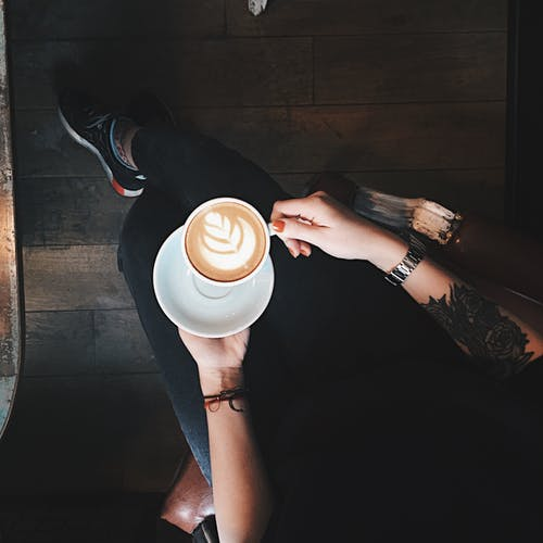 Top View Photo of Person Holding Coffee Cup