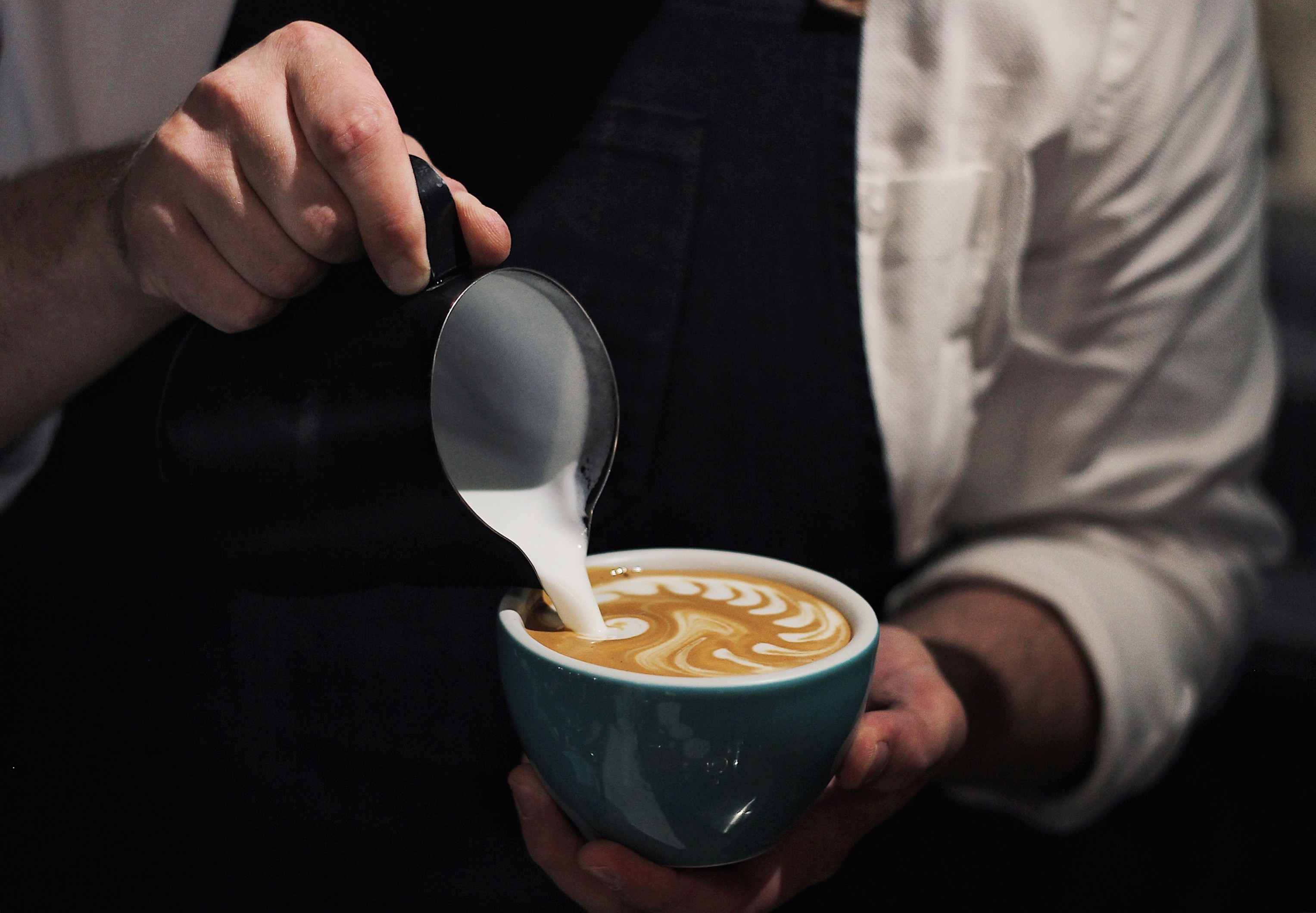 Close-Up Photo of Man Pouring Milk In Coffee