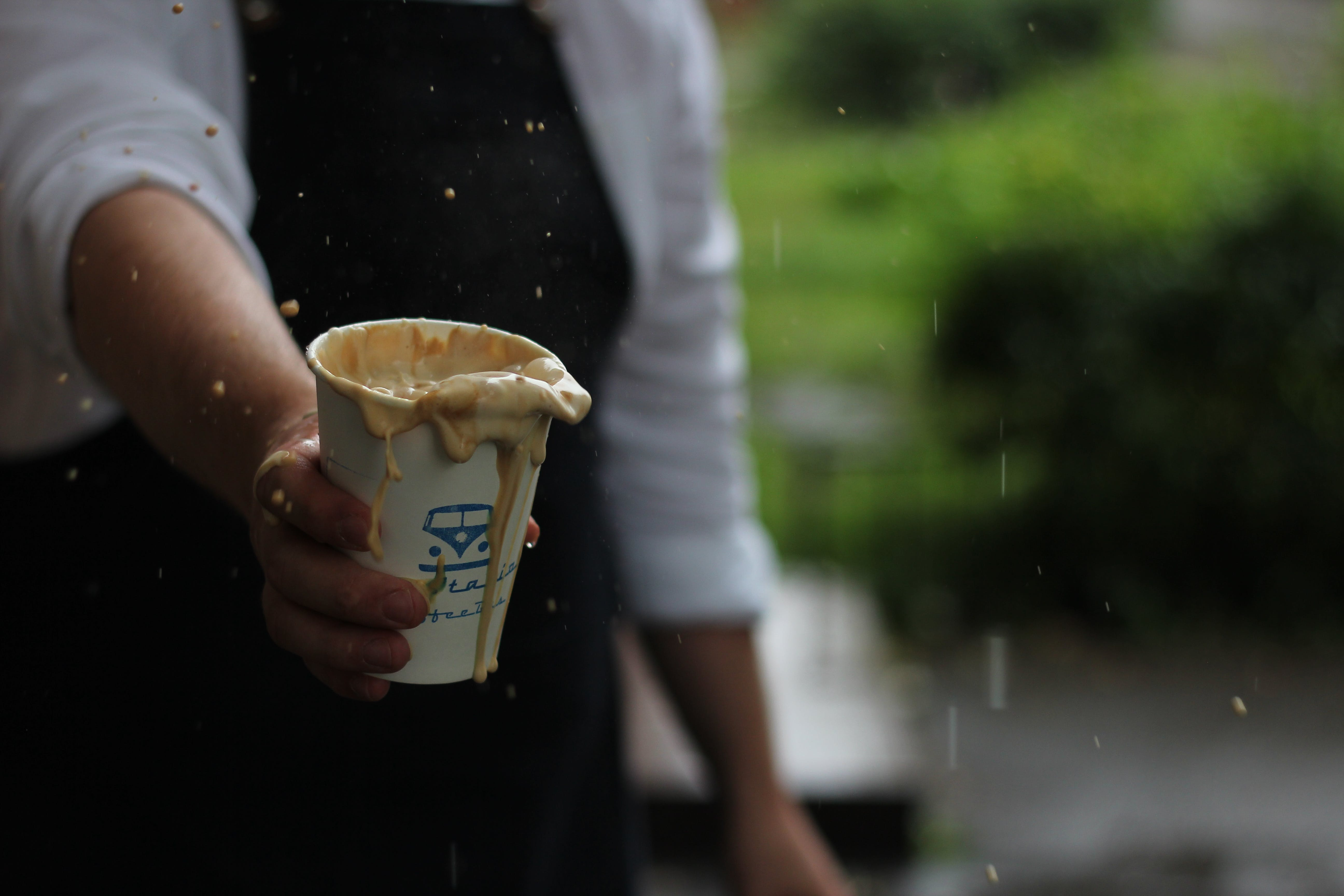 Person Holding Messy Ice Cream on Cup