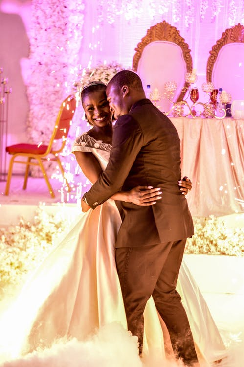 Man In Black Suit And Woman In White Wedding Gown Dancing