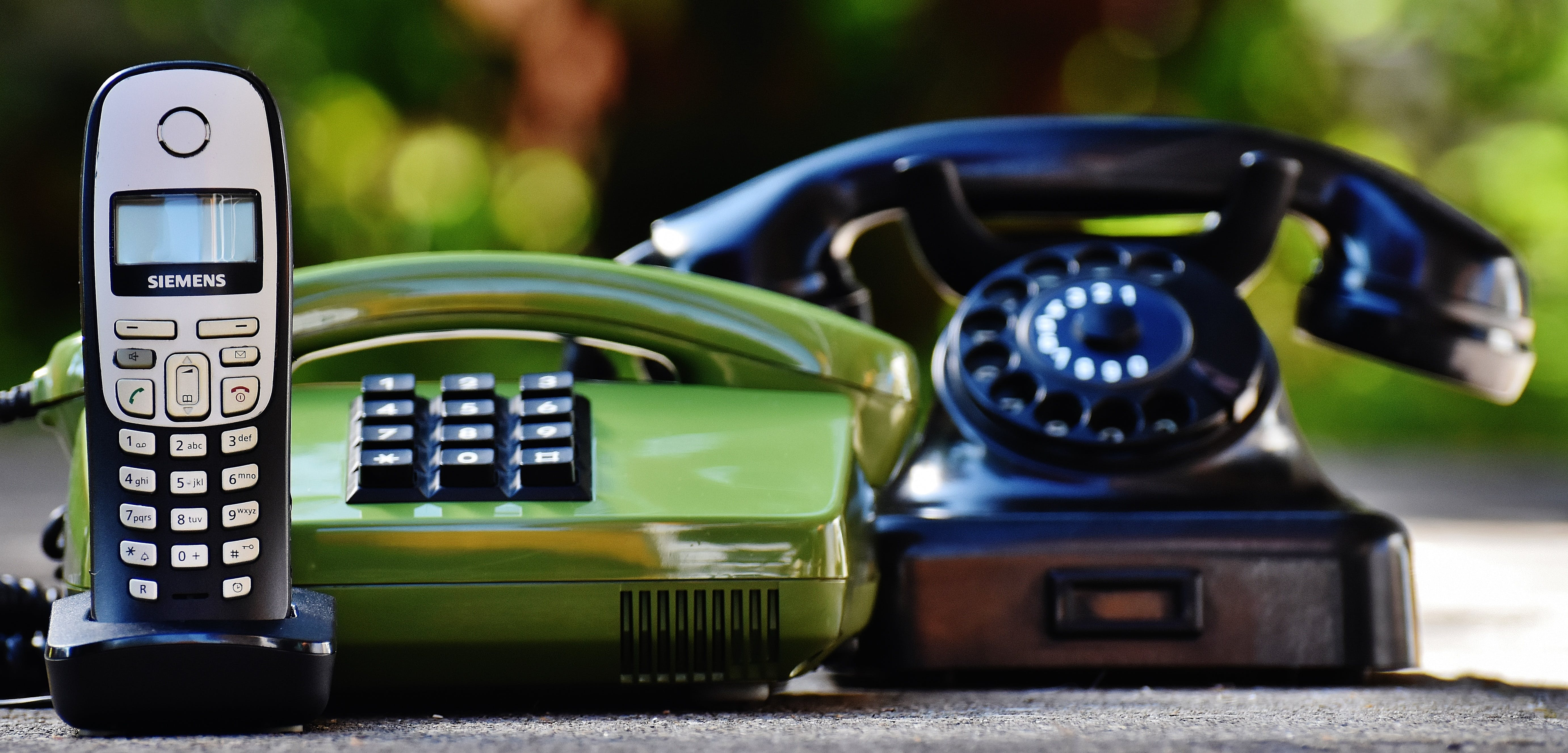 Black and Green Rotary Telephones Beside Cordless Home Telephone