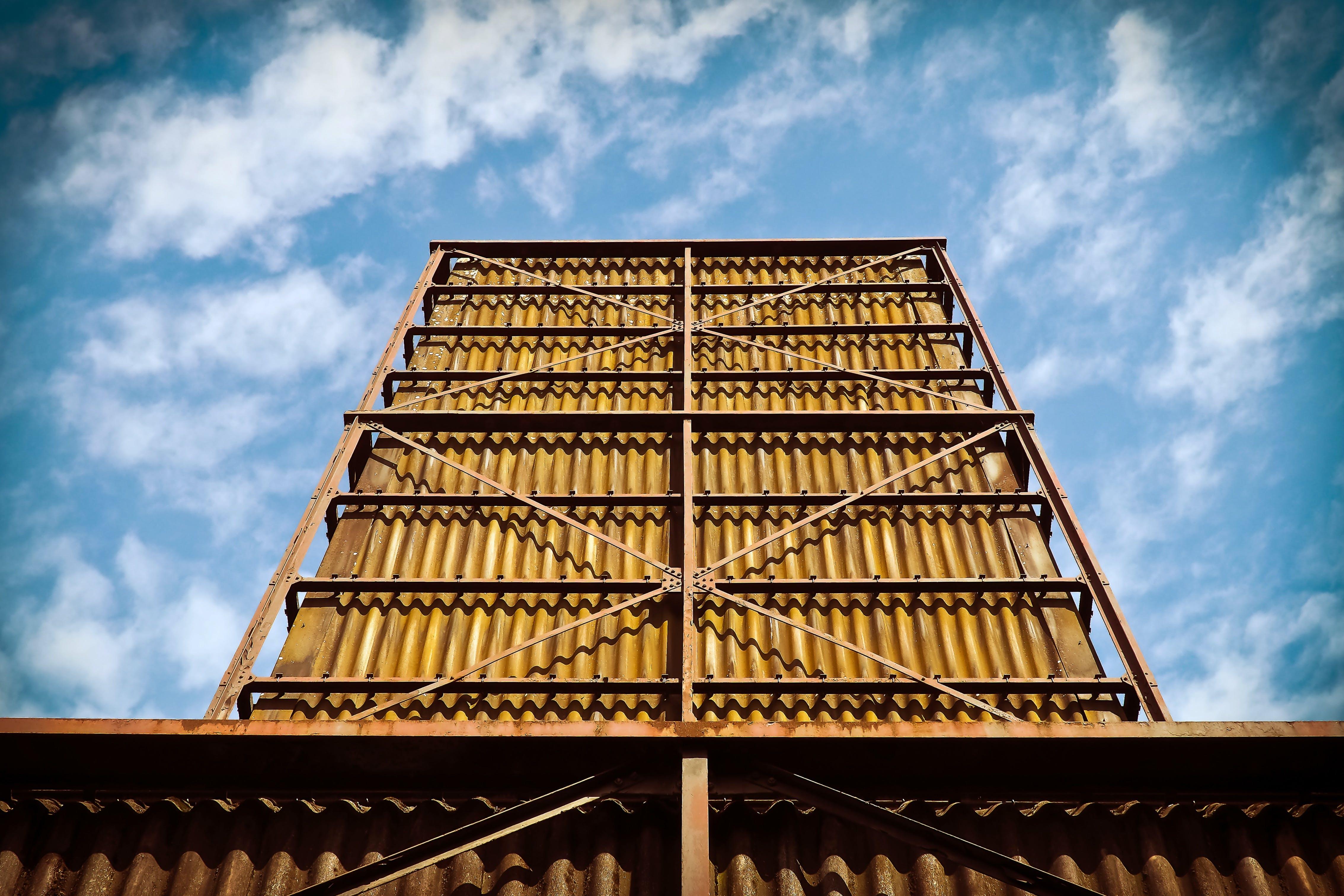 Brown Metal Building Under Cloudy Sky