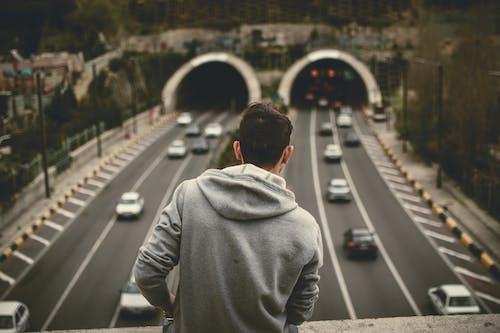 Man in Grey Hoodie Standing on Bridge over the Expressway