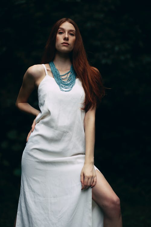 Woman Wearing White Dress and Blue Beaded Necklace