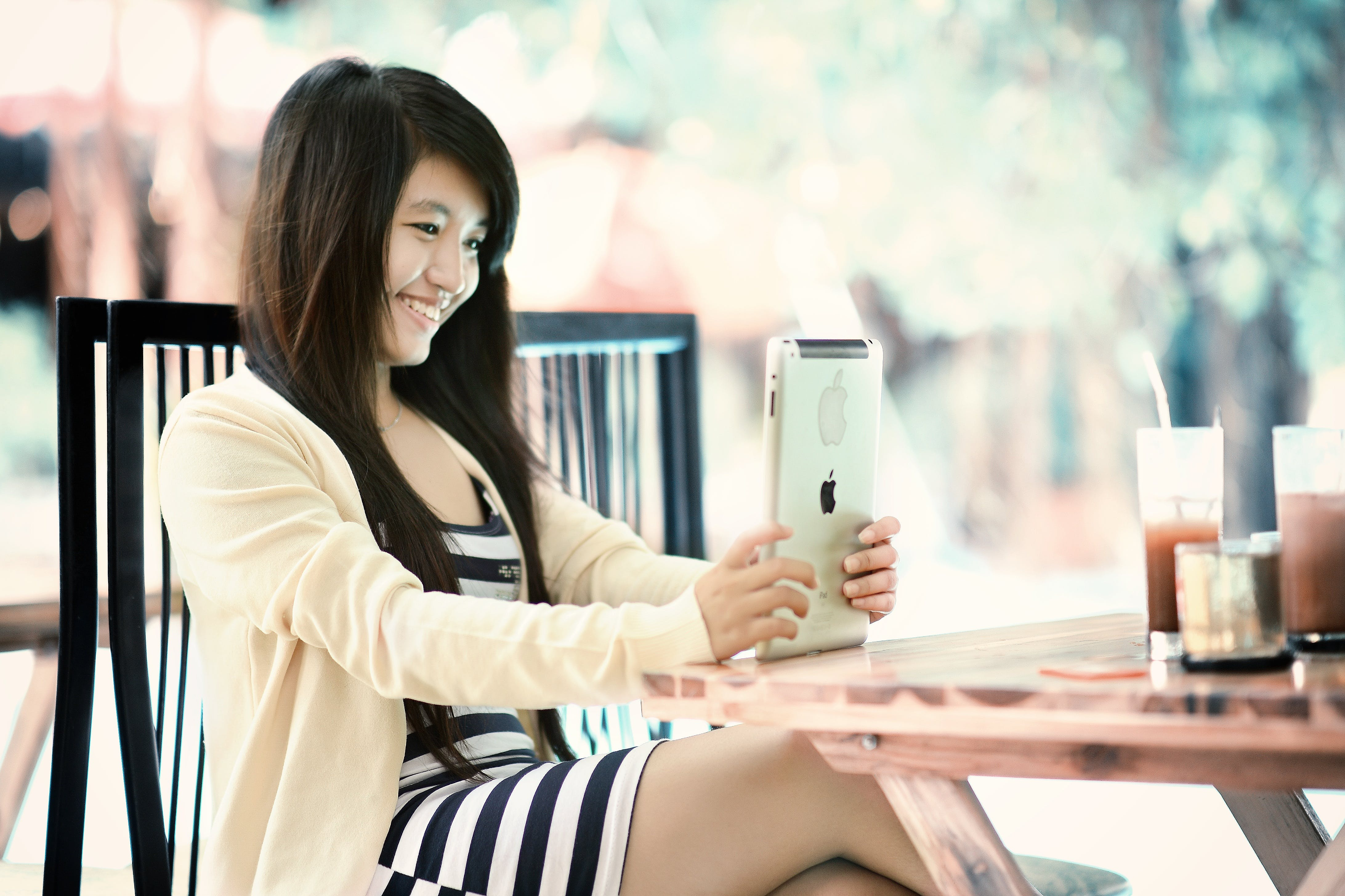 Woman Smiling While Sitting in Front of Table and Using Gold Ipad