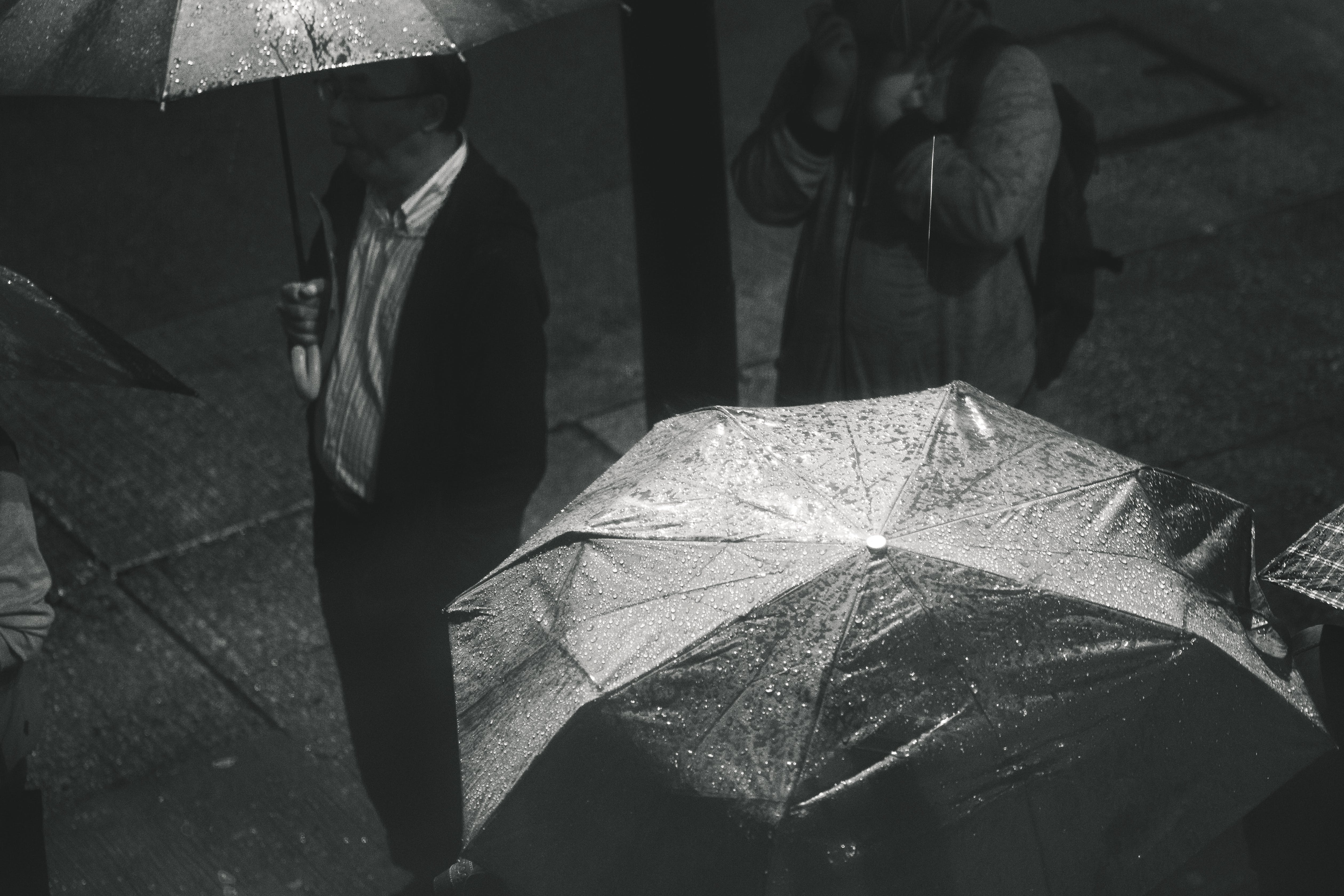 Greyscale Photo of Man Holding Umbrella While Raining