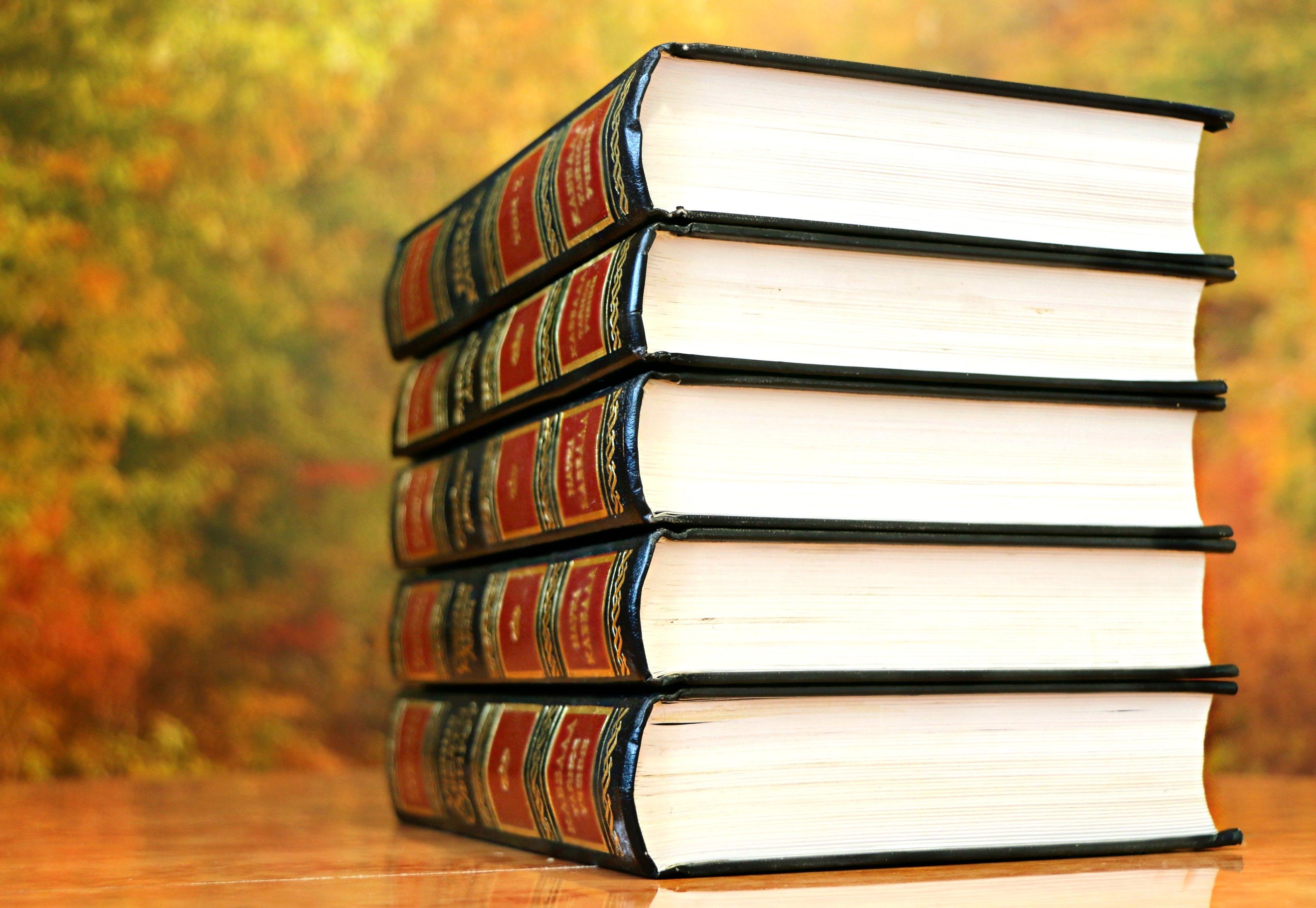 Five Hardbound Books on Brown Surface