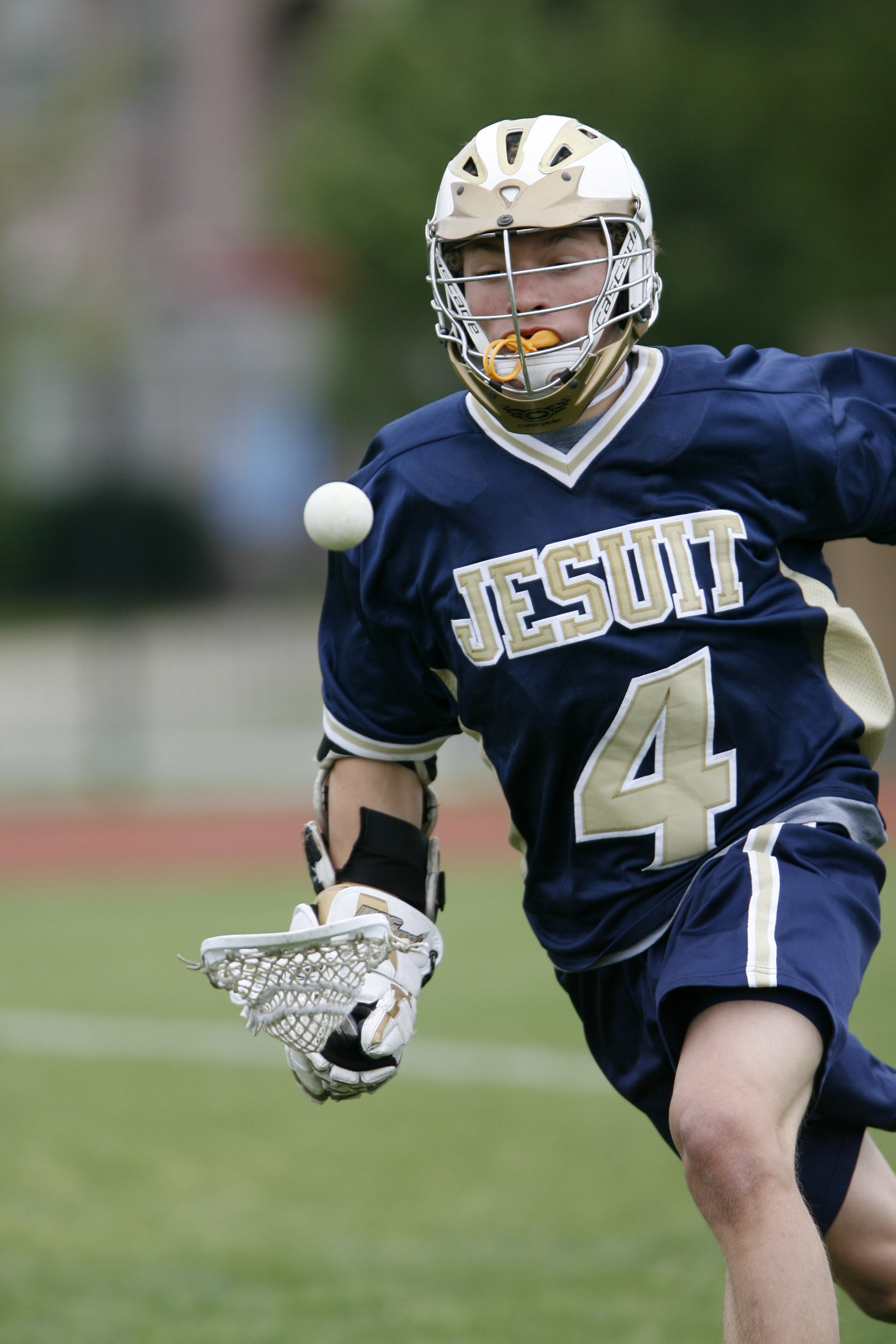 Man Holding Lacrosse Stick Running on Field during Daytime