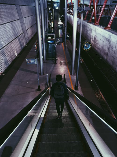 Person With Backpack Riding Escalator