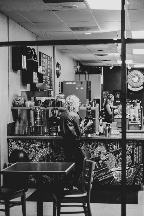 Grayscale Photo of Woman Standing Near Counter