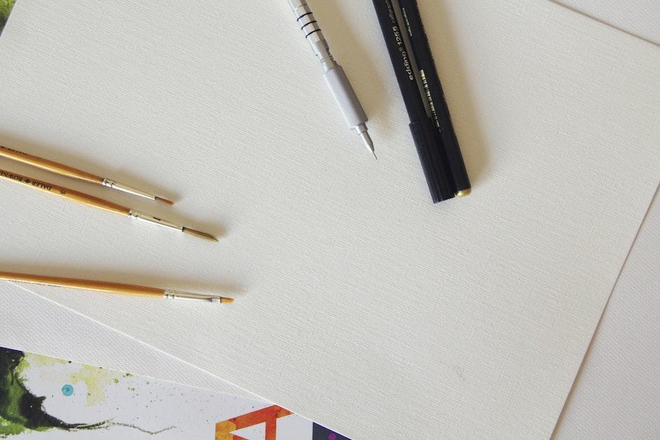 Brown Paintbrush Beside Black and Silver Ballpen on White Printing Paper