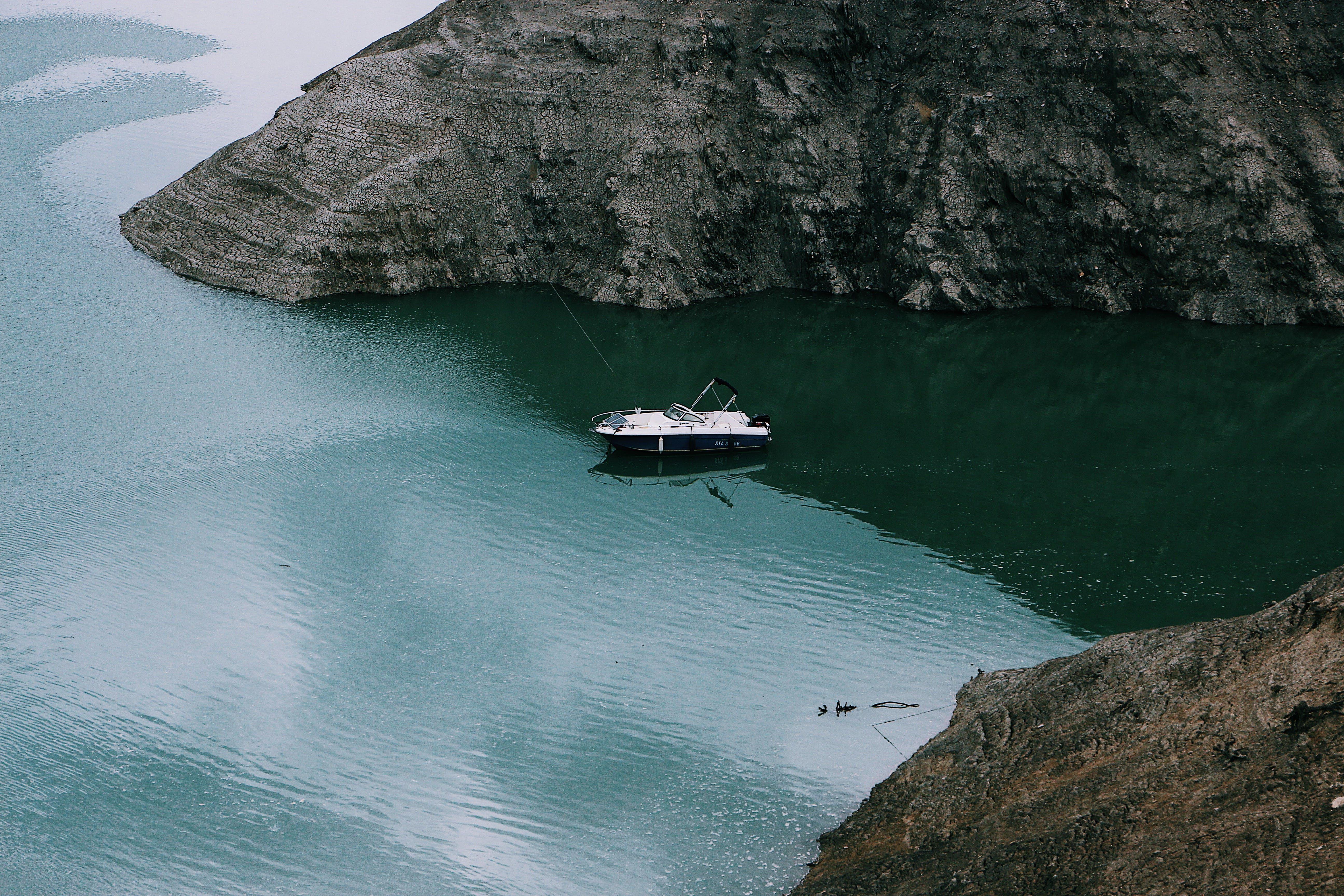 White Boat Sailing Near Cliff