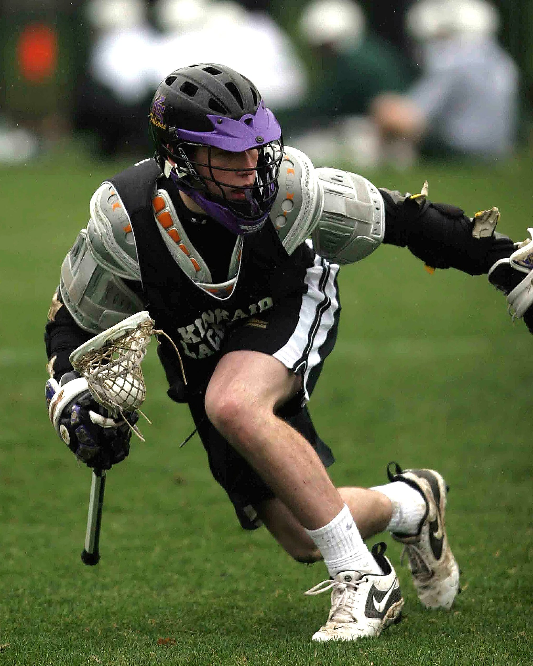 Person in Black Sports Jersey Playing Lacrosse