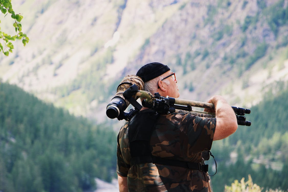 Man Carrying Camera With Tripod