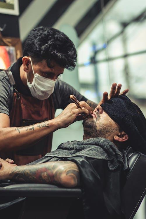 Man Shaving Man's Beard Using Straight Razor