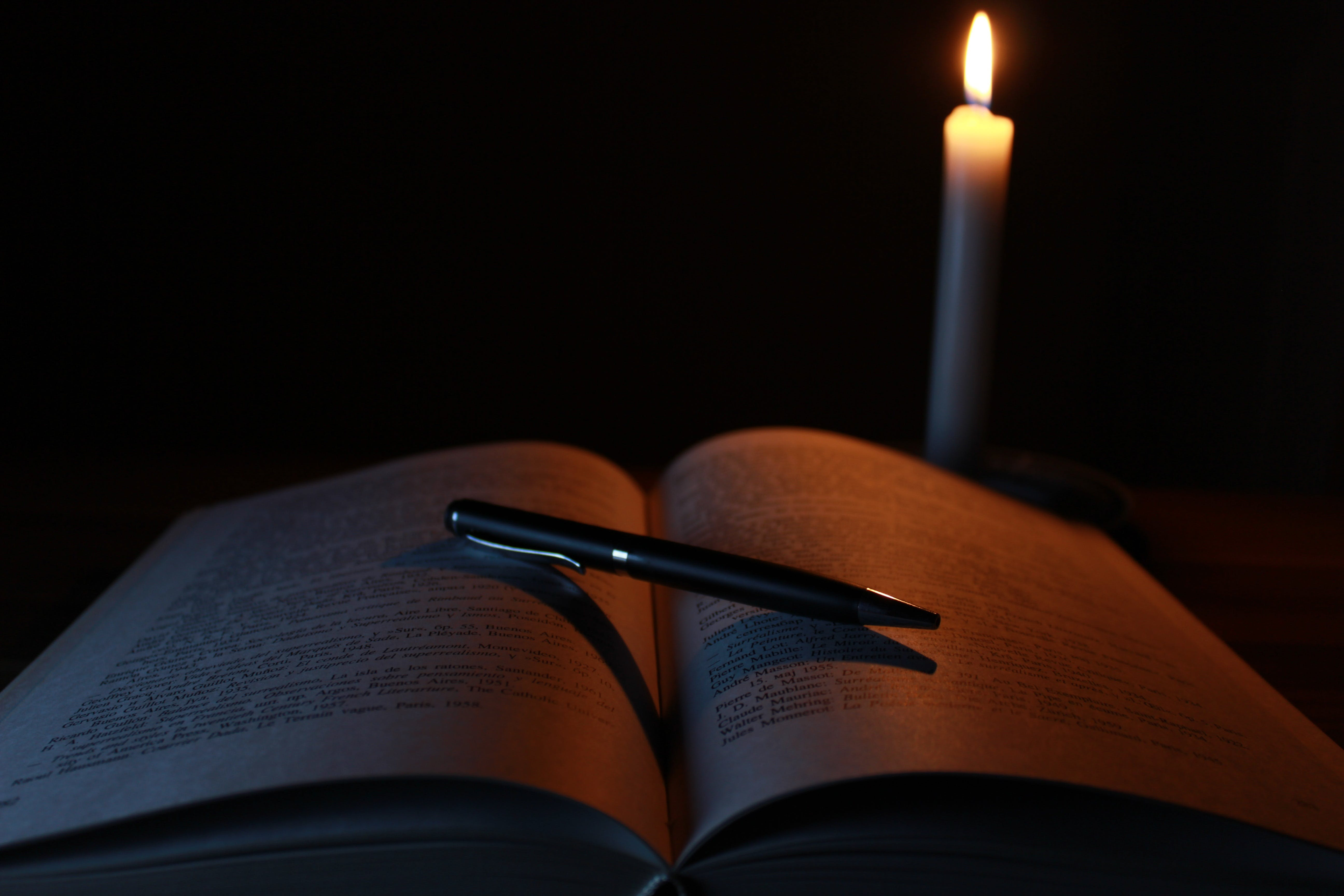Black Pen on Opened Book Beside Lit Taper Candle