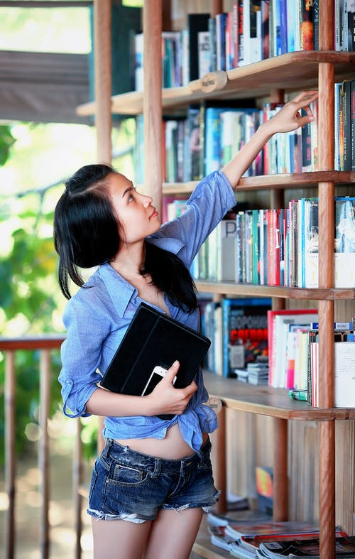 Woman Reaching Book Near Handrail