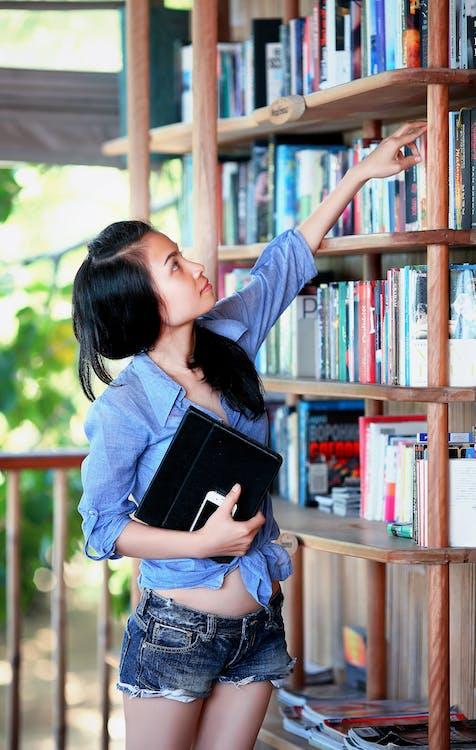 Woman Reaching Book Near Handrail