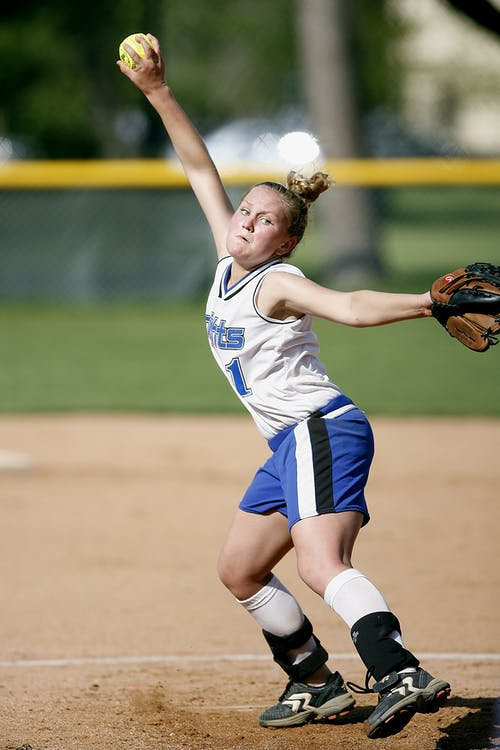 Full body determined professional female softball pitcher in sportswear and glove throwing baseball from pitcher mound during dynamic game on stadium
