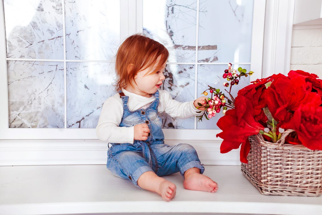 Kid's Blue Denim Jumper Sitting on White Wooden Side Table