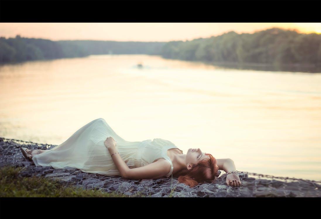 Woman Lying Near Body of Water