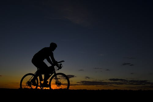 Man Riding Bicycle during Nightfall