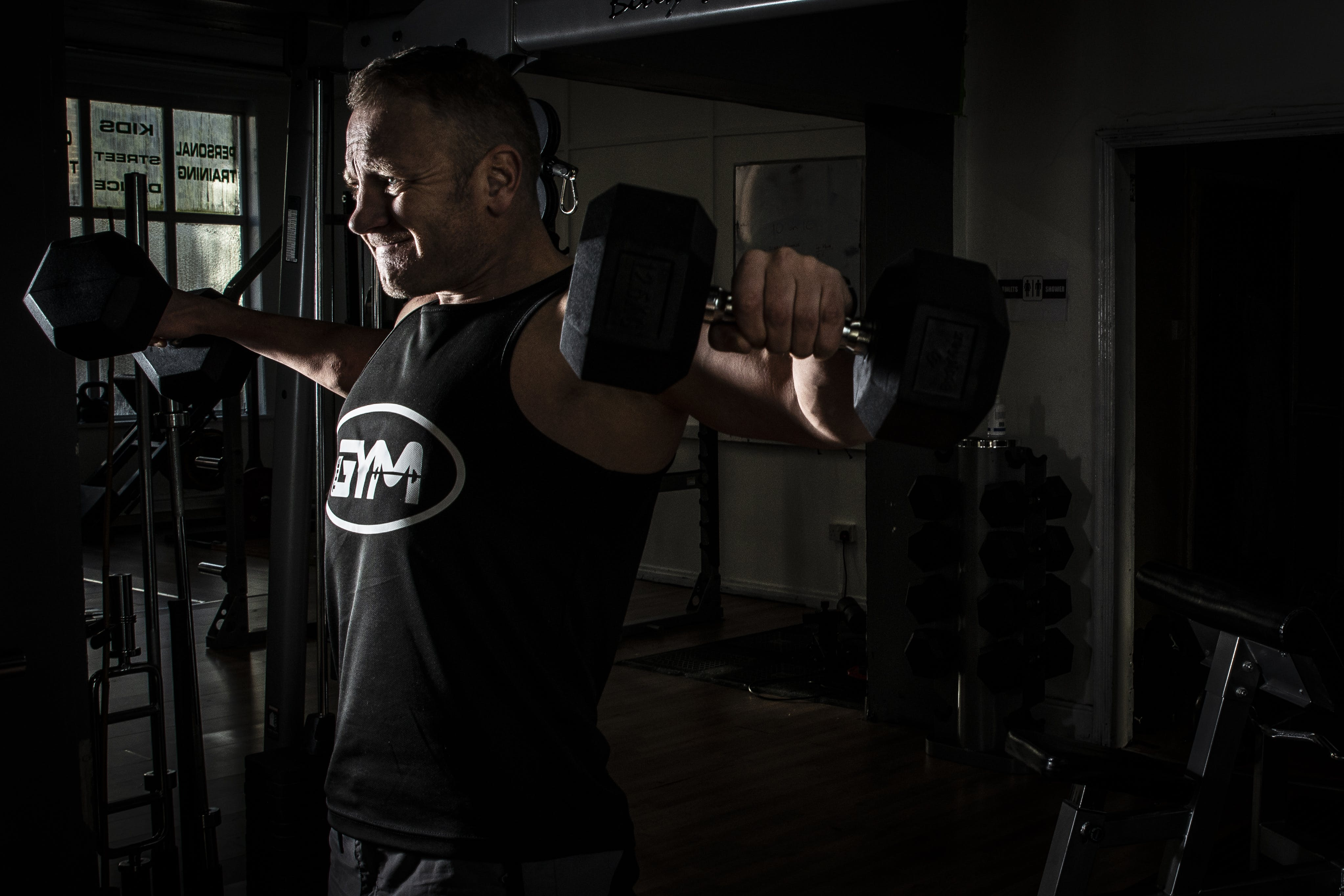 Man Exercising at the Gym With Fixed Weight Dumbbells