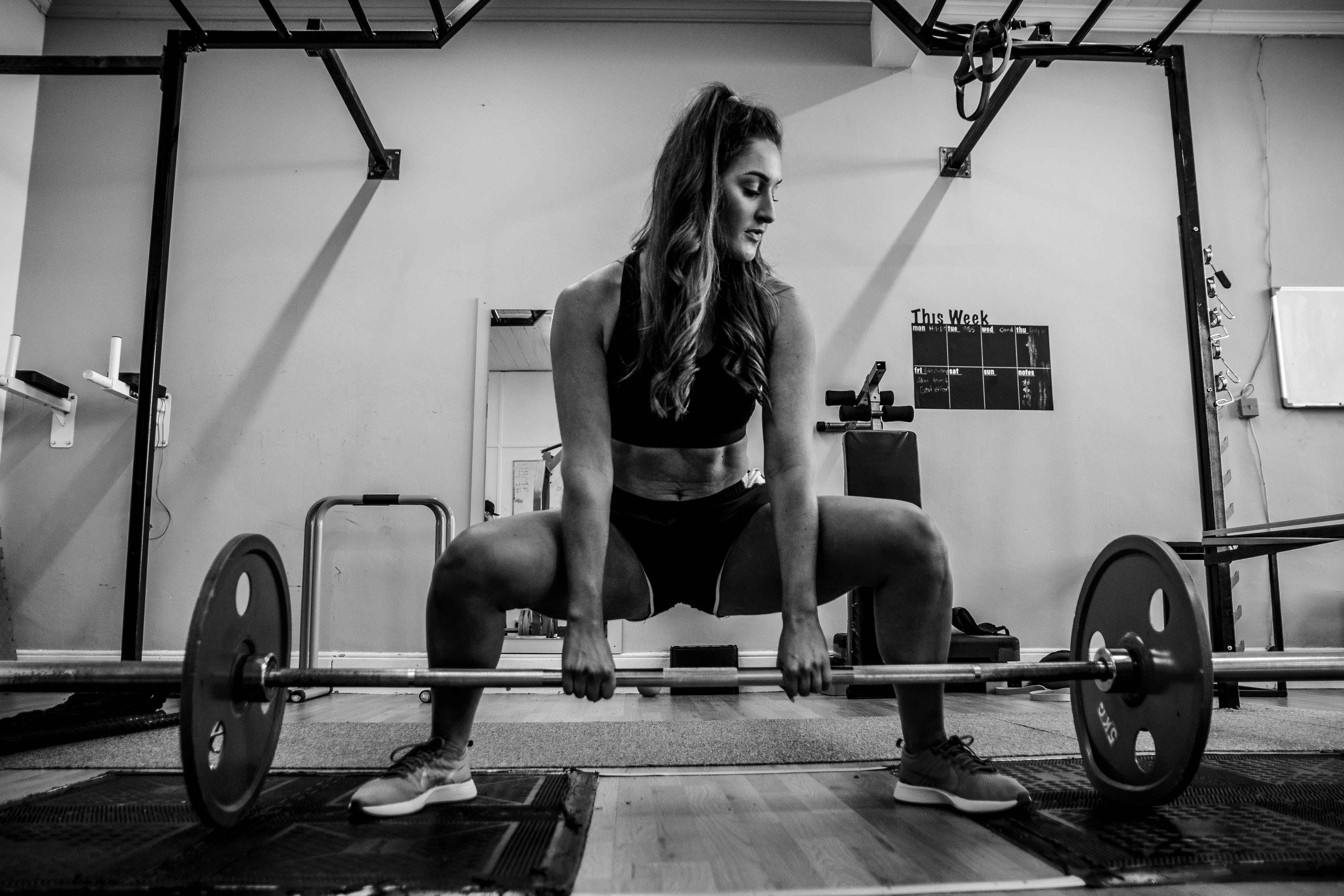 Woman About to Lift a Barbell Off the Floor Inside Gym