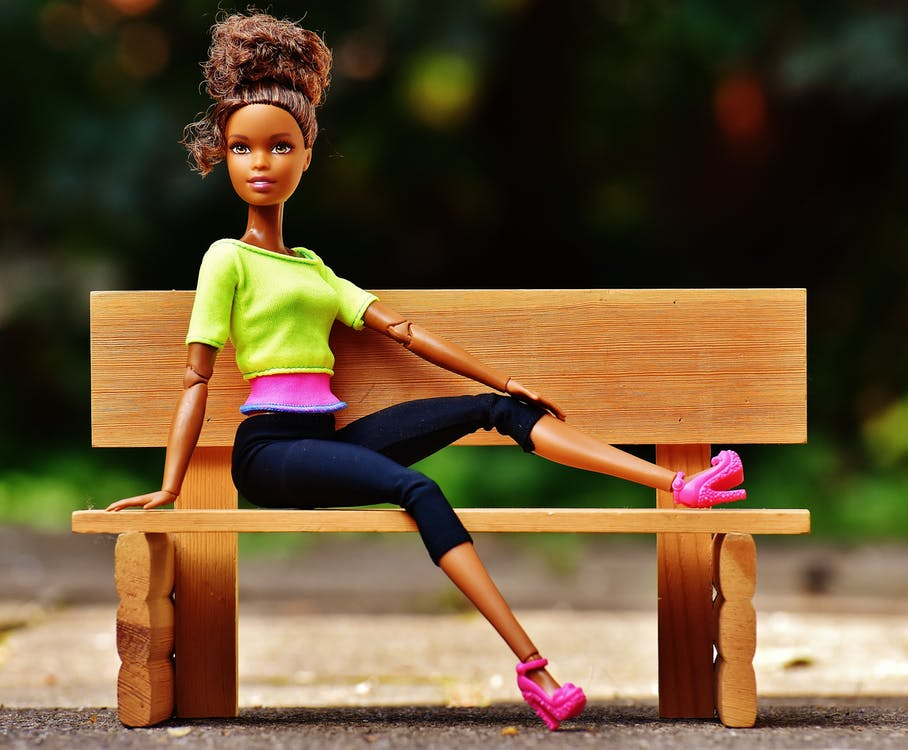 Doll Sitting on Brown Wooden Bench