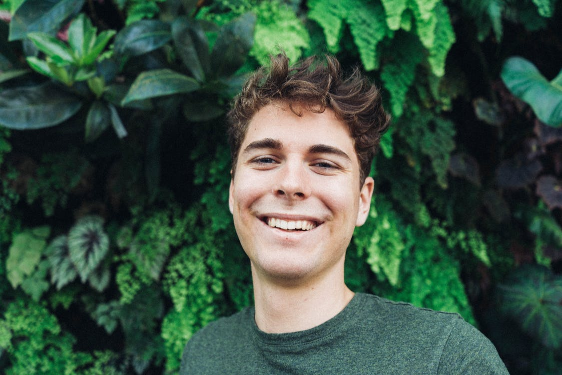 Smiling Man in Front of Green Plants