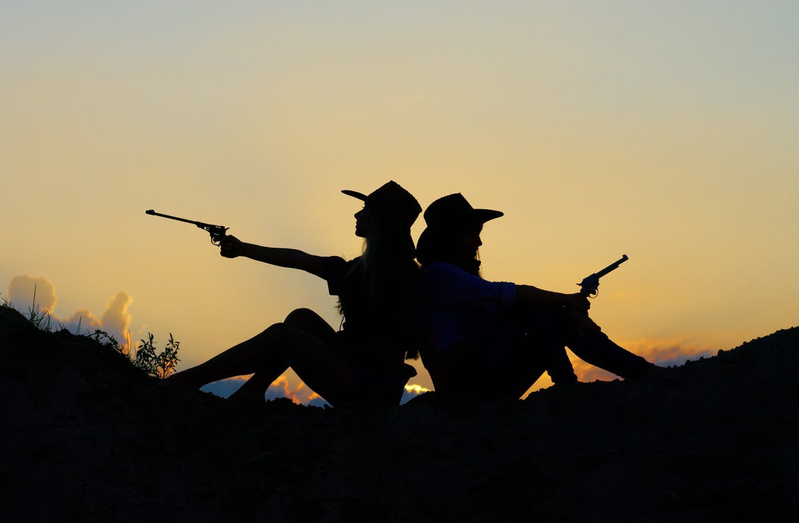 Silhouette of Two People Holding Revolver Pistols Sitting on Hill