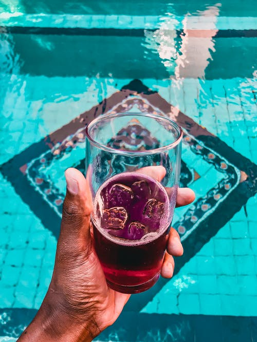 Person Holding Glass of Purple Beverage