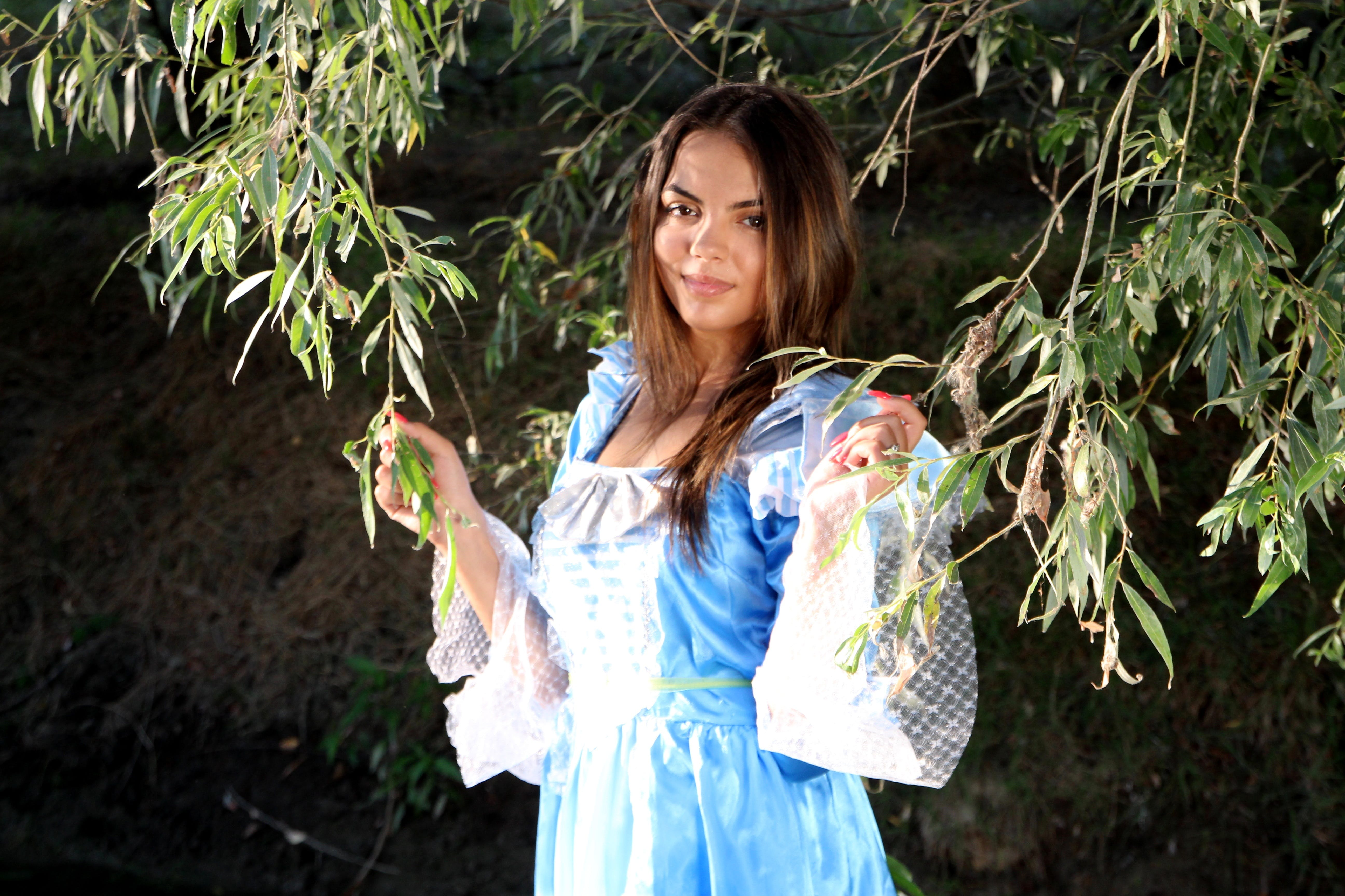 Woman in Blue Dress Holding Tree Branches