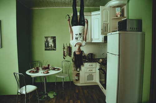 Woman Standing on Ceiling Inside Room
