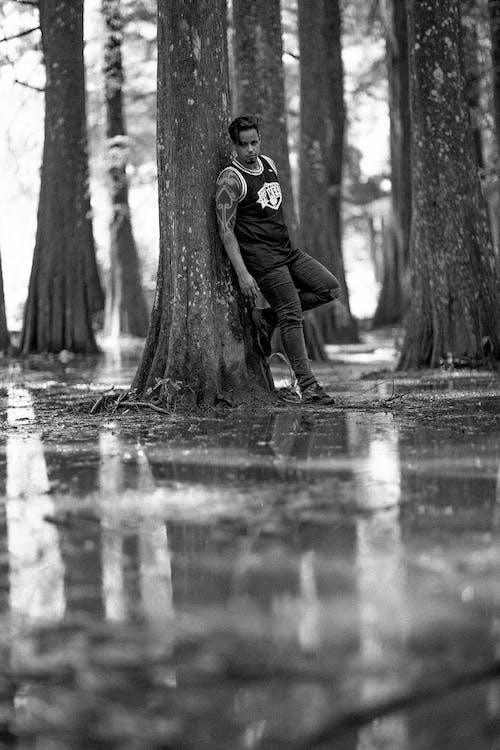 Graustufenfotografie Des Mannes, Der Gegen Baum Lehnt
