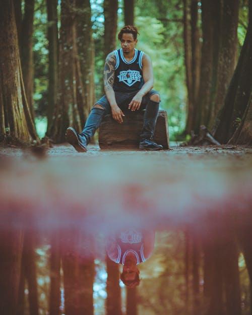 Man Sitting on Wood Log