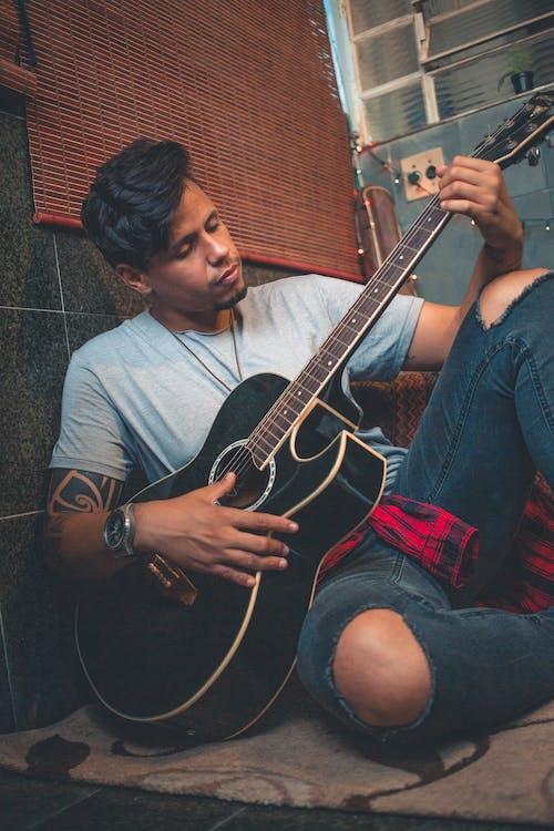 Kostnadsfri bild av gitarr, gitarrist, ha på sig, instrument