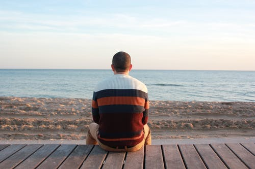 Man Sitting on Wooden Panel Facing in the Ocean