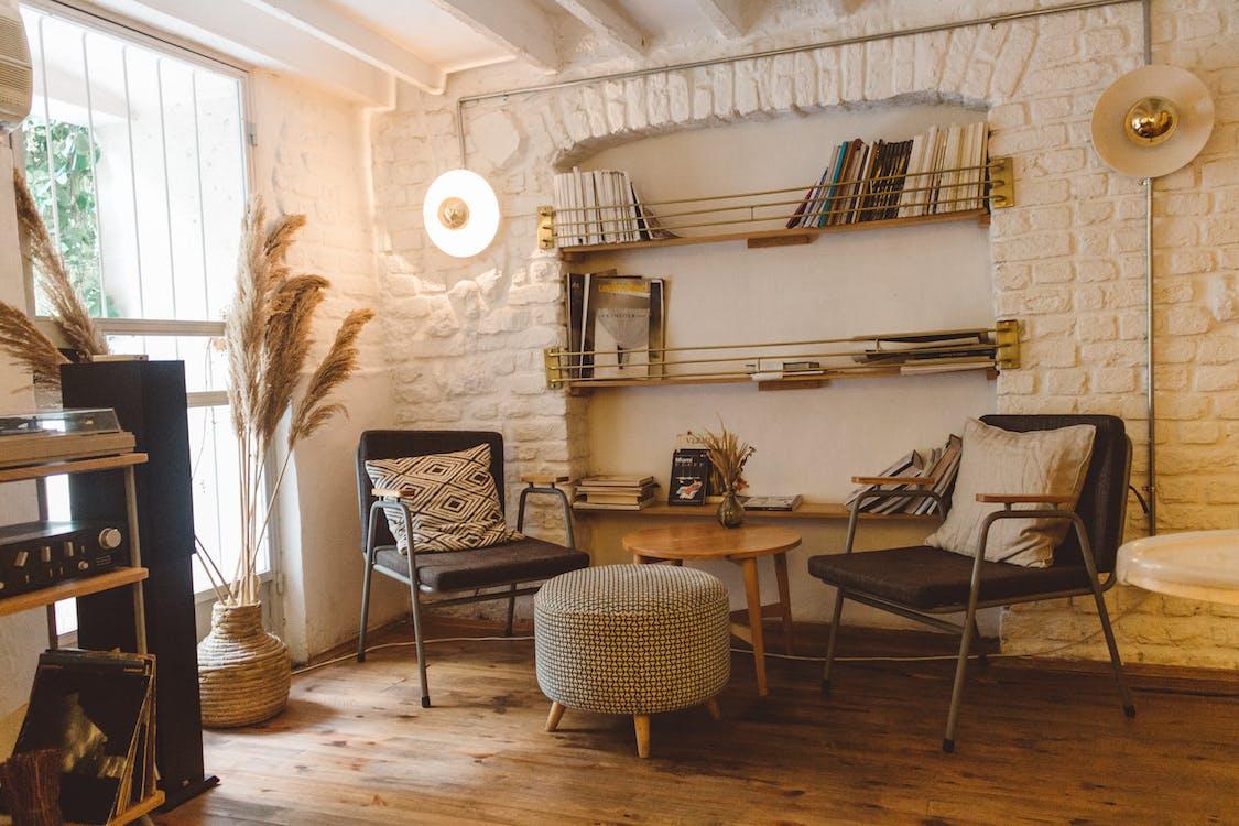 Runder Brauner Holztisch Zwischen Zwei Stühlen Und Osmanischem Stuhl