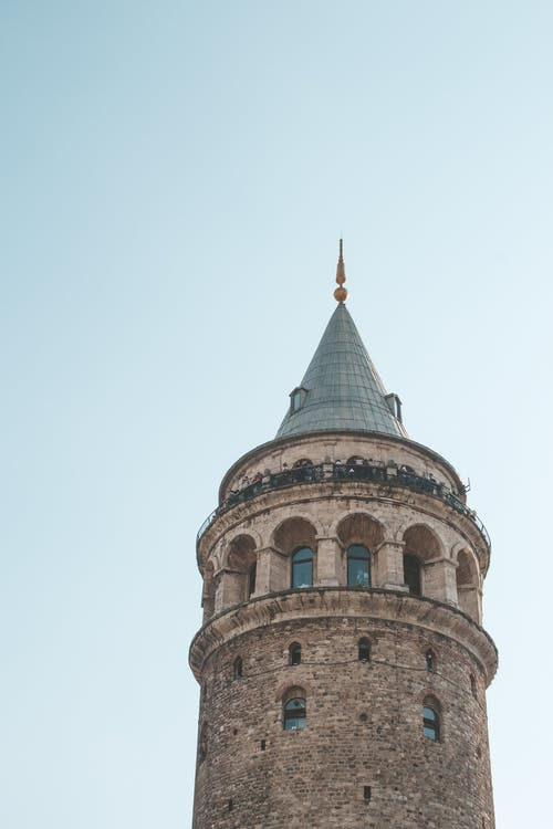 Low angle exterior of majestic old cone capped Galata Tower in Istanbul with arched windows against cloudless blue sky