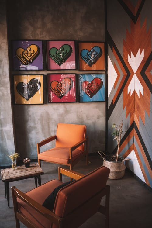 Two Orange Armchairs and Assorted-color Heart Wall Decors