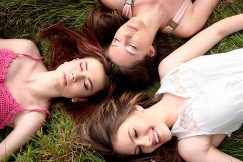 Three Women Lying on Green Grass