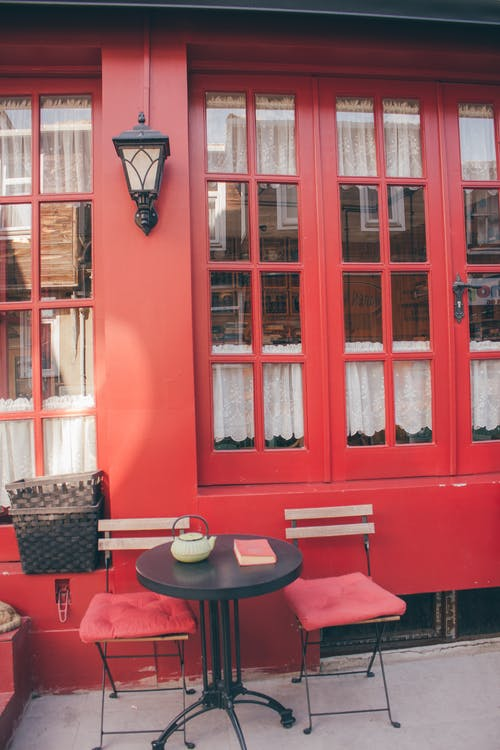 Patio Bistro Set Beside Red Wall