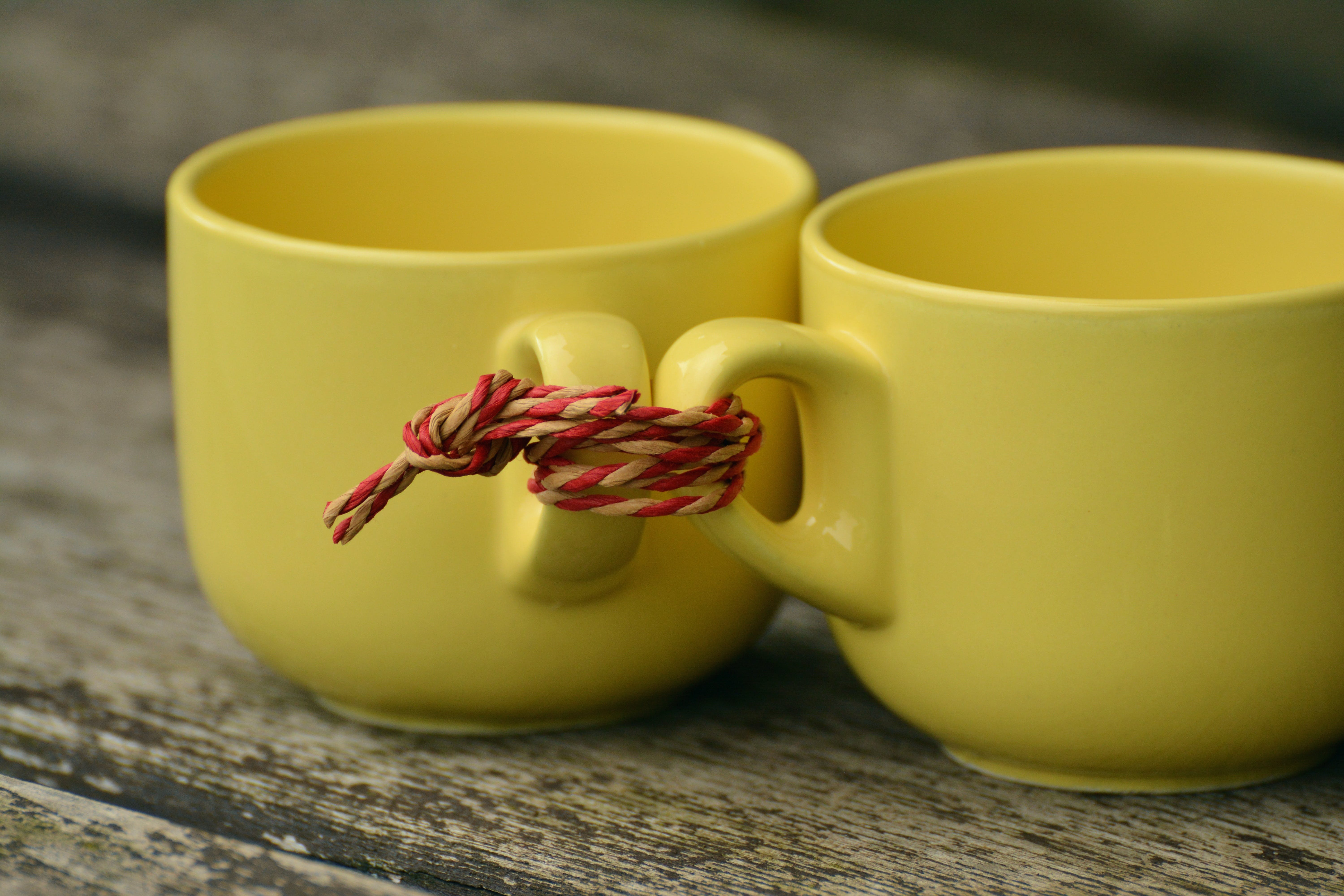 Two Yellow Mugs Tied Together With Rope