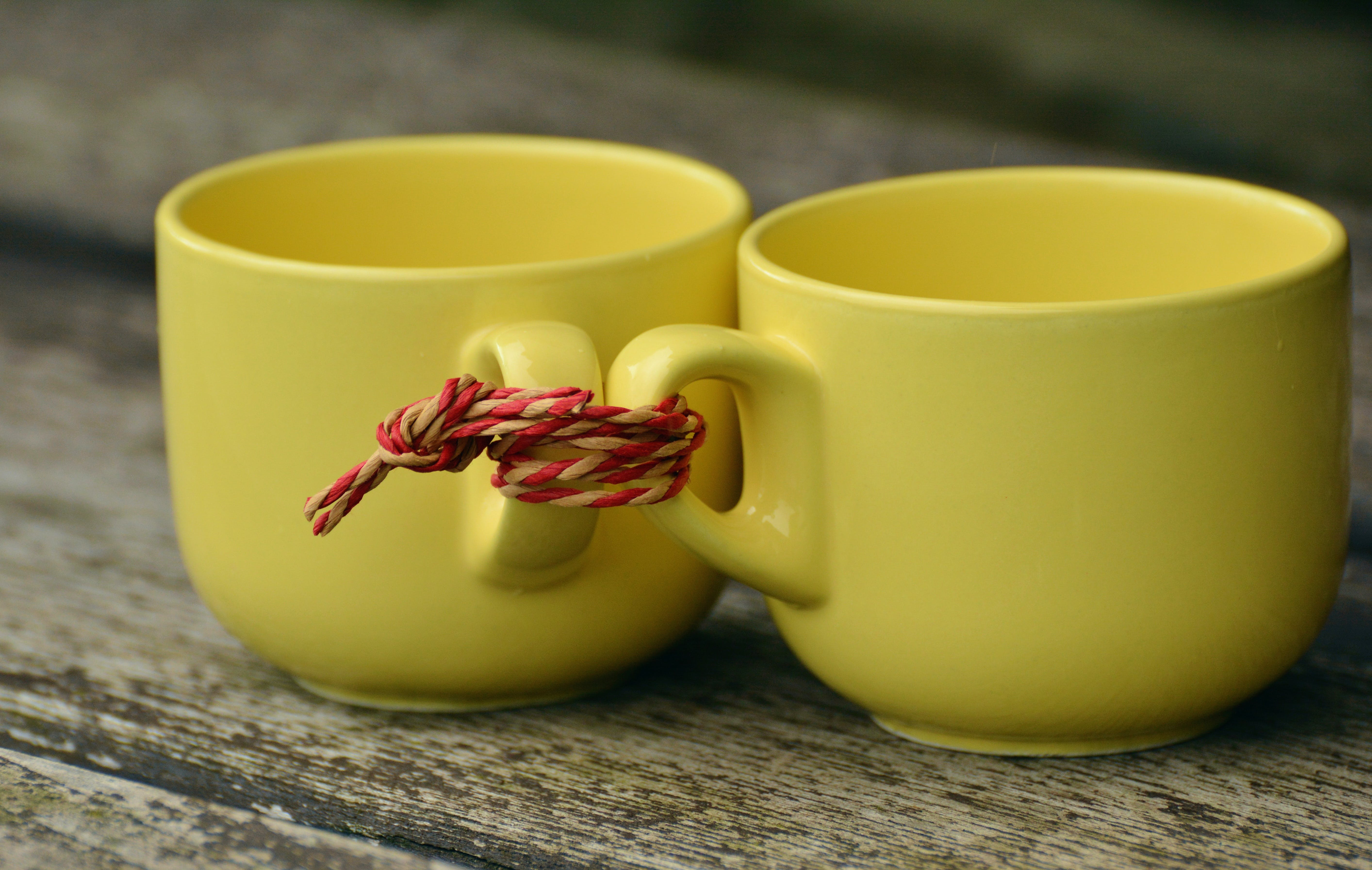 Two Yellow Mugs on Brown Wooden Surface