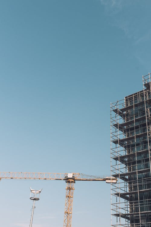 Construction crane against building with scaffolding