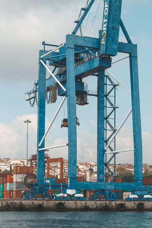 Contemporary dockside cargo crane located on industrial embankment in port on clear day